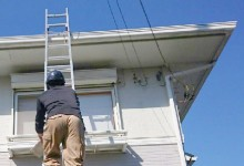 はしごに登り家を見る作業員