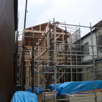 A様邸の建前後の写真。屋根の下地板を施工した段階で、外壁は無く、屋根のルーフィングもない。手前には店舗部分の基礎が囲われている。