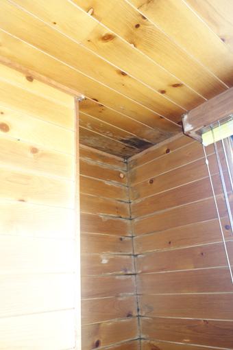 木の小幅板を張った様な壁の、入り隅部や目地などが黒ずんでいる。