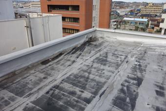 屋上のシート防水は浮き上がり波打っている。切れ目も見える。
