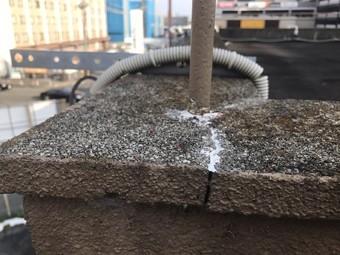 パラペットのコンクリート笠木に設置された手すりの支柱。支柱を起点としたひびが走っている。
