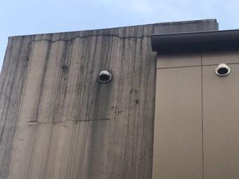 下から見上げると、外壁上部に亀裂や雨筋汚れが見られた。