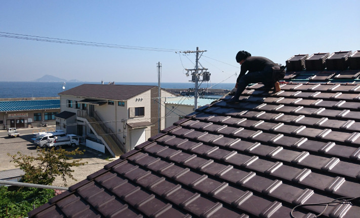 三重県鳥羽市答志島の屋根葺き作業。奥に見えるのは伊勢湾。