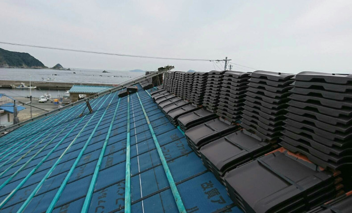 K様店舗上段の防水が終わった屋根に瓦を並べていきます。