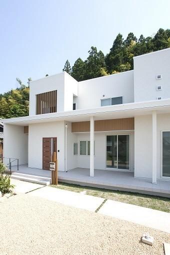 青い空と豊かな緑地を背景に映える、真っ白な四角い外観の木造住宅