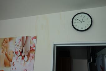 時計の掛かる白い壁紙に変色が見られる。
