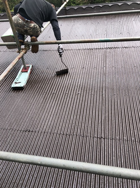 トタン屋根にローラによる塗装作業