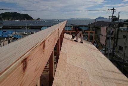 差し掛け招き屋根に板が張られて形が見えてきました。遠景に伊勢湾の水面が見えます。