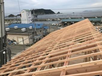 三重県鳥羽市答志島から東方の海を望む現場。屋根の垂木が整然と並んでいます。