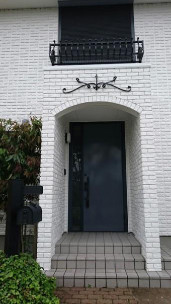 ポーチの上にアイアンの壁面装飾を設置し、二階の窓にもアイアンのフラワーボックスを合わせた。