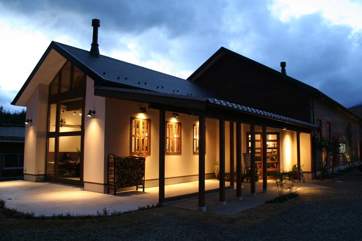 夕方に明るい光を湛えたパティスリーカフェの外観。