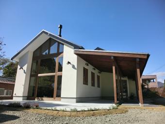 白い塗り壁の切妻屋根と、差し掛けられた大きな庇。妻側の壁に床から天井までの大きな開口を持ち、垂木を見せた庇は瓦葺き。